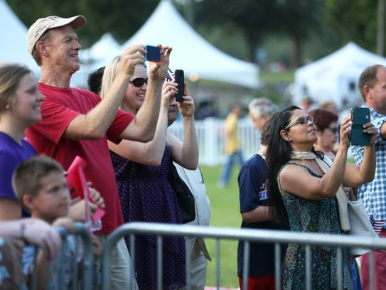 People watch and film on their phones as 14 new citizens
