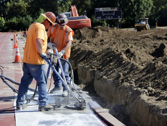 Construction workers remove parts of the track at Tulare's