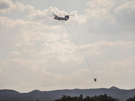 A helicopter brings water to the Roach Fire in Dudleyville,