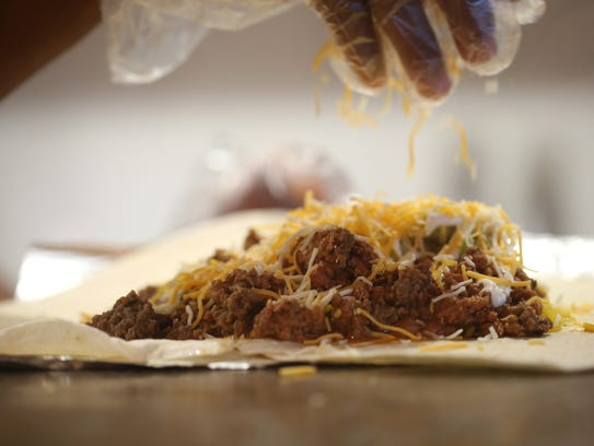 Shredded cheese is sprinkled on a beef burrito at LOL