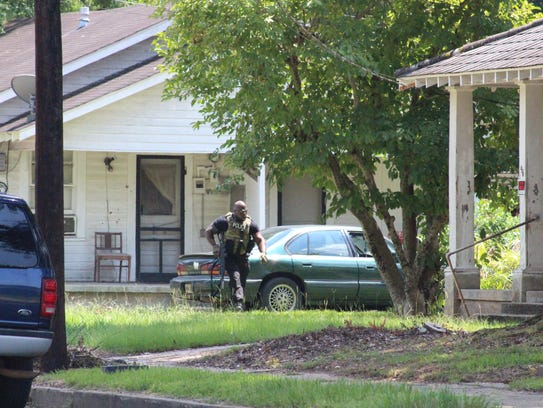 An officer moves into position at a shooting scene