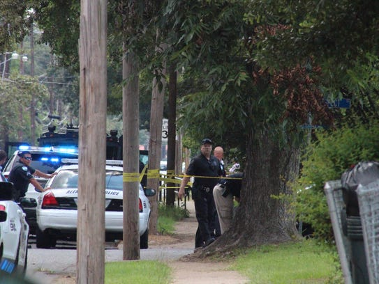 Crime scene tape is wrapped around a Monroe Street