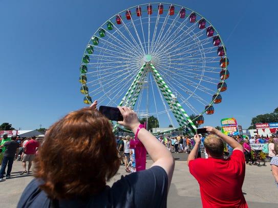 Fairgoers photograph a Ferris wheel at State Fair Park