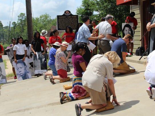 Civil rights pilgrims kneel in prayer Saturday as they
