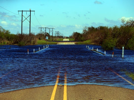 Water floods a road after Hurricane Harvey made land
