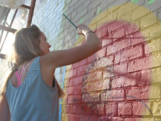 Jessica Kopecky paints the petals of a flower for her
