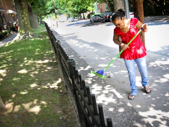 PROVIDENCE: Nelie Rodriguez sweeps the sidewalk along
