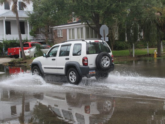 A vehicle drives on a flooded street in Charleston