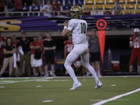 Iowa City West quarterback Evan Flitz drops back for