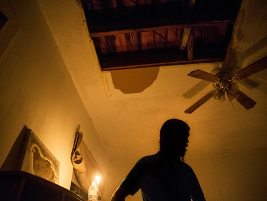 Matthew Tyler, 35, stands below a hole in his roof,