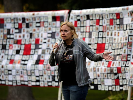 Bev Kelley-Miller speaks Sept. 10 in front of three quilts showing the Wisconsin faces of addiction and recovery during the Fox Cities Lights of Hope gathering at City Park in Appleton.