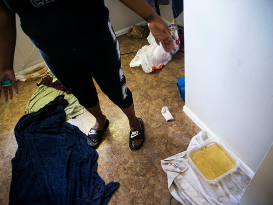 A resident points out the water damage and the containers