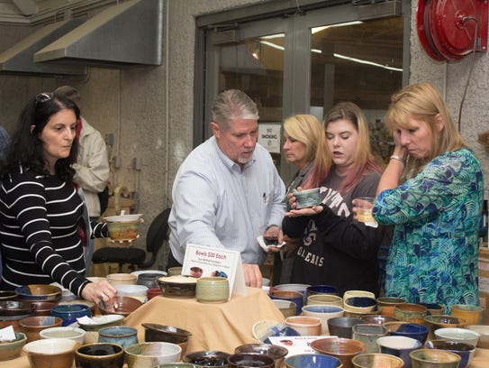 Guests select from handcrafted bowls at a previous
