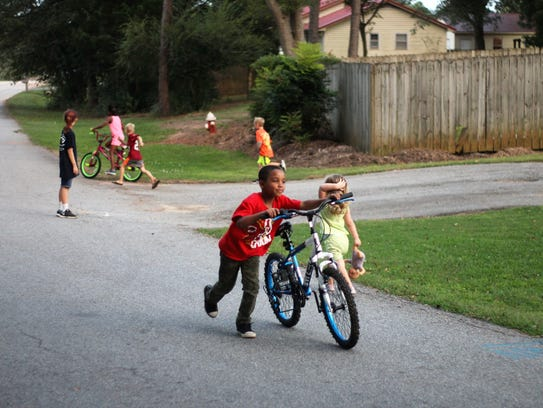 Cayden Dennis pushes his new bike, a replacement from