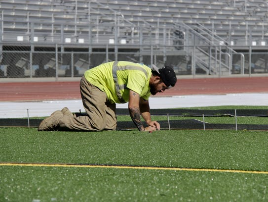 Cameron Crow, Exeter native, works to install artificial