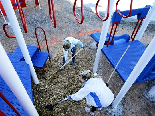 Ana Vicker, left, and Meghan Borowski spread wood chips