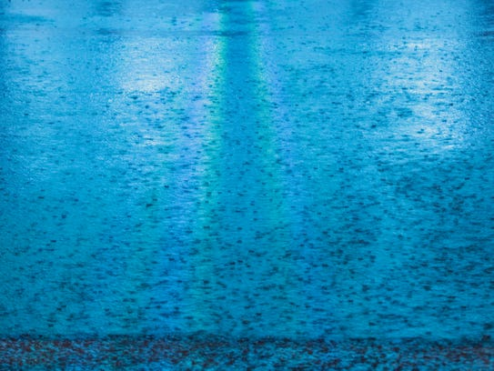 Rain drops fall on a flooded street in downtown Mobile,