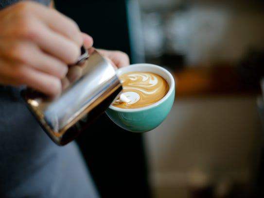 Co-owner Austin Ferrari pours milk foam into a cappuccino