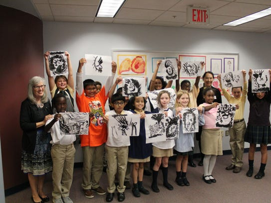 Fourth grade students proudly display the painting