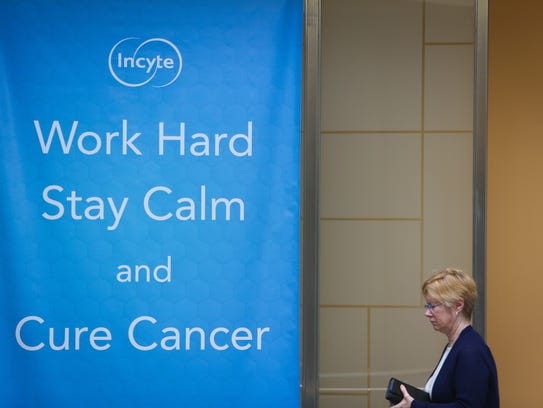 An employee walks by an Incyte company motto banner