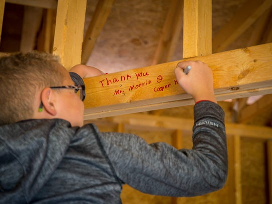 Cooper King, 9, of Wisconsin, writes on the walls of