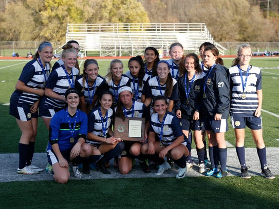 Notre Dame players hold their championship plaque after a 2-1 win over Trumansburg in the Section 4 Class C final Oct. 28 at Norwich High School.