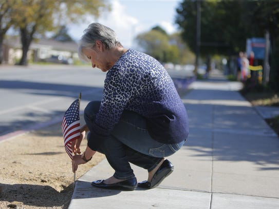 Katherine DeSalvo places a flag on the ground outside