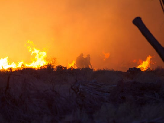 Firefighters battle flames Tuesday evening in Desert