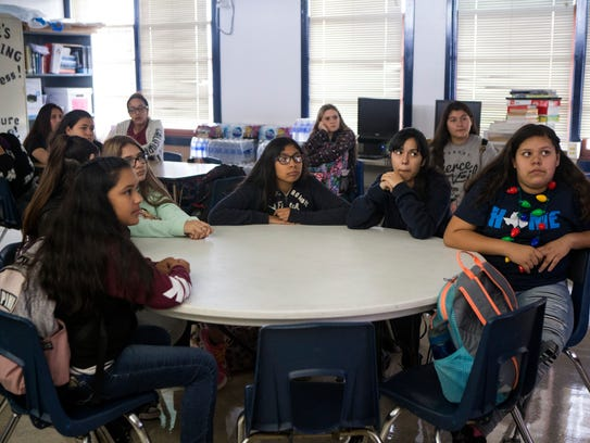 A group of seventh-grade students listen to an anti-bullying