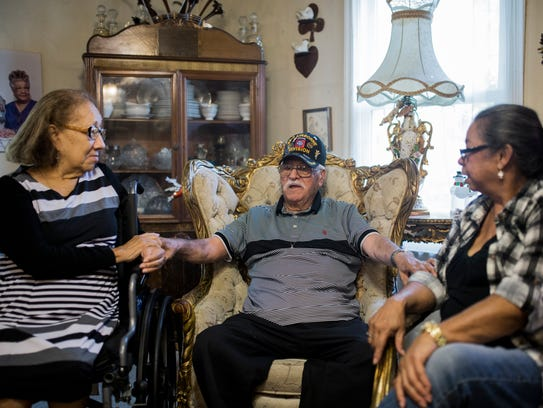 John Duran, 93 (center) embraces his daughter Evelyn Bracy (right) and stepdaughter Maria Lus Sanchez (left) on Monday, Dec. 11, 2017 as he speaks about serving in the Army during World War II. Duran was recently reunited with daughter Evelyn Bracy after being separated from her when she was seven.