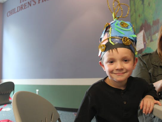 Kaiden Wentworth, 7, smiles in the hat he created during