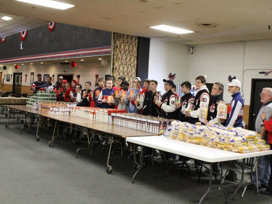 Members of the Westland John Glenn High School wrestling team with other volunteers packing holiday food boxes for area veterans at the Wayne-Ford Civic League.