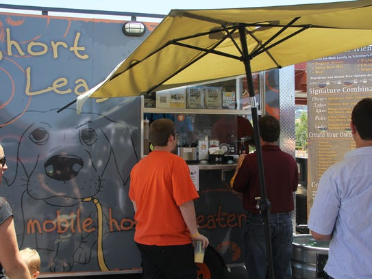 People order hot dogs from the Short Leash food truck during Food Truck Friday at the Phoenix Public Market on May 11, 2012, in Phoenix.