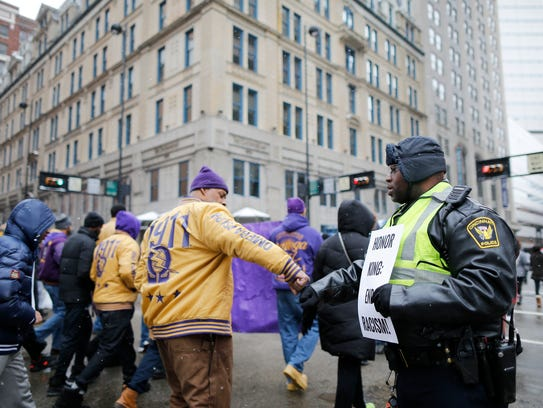 Marchers thank police officers for their service during the Martin Luther King Jr. Day march in downtown Cincinnati on Monday, Jan. 15, 2018.