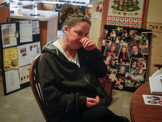 Sandy Emberlin of Des Moines wipes tears away as she
