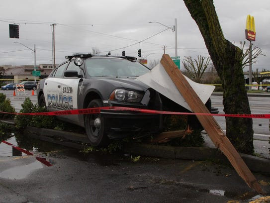 A Salem Police patrol car rests against a plank of