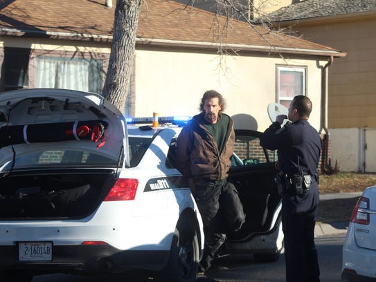The shooting suspect waits in handcuffs on 2nd Avenue South in Great Falls
