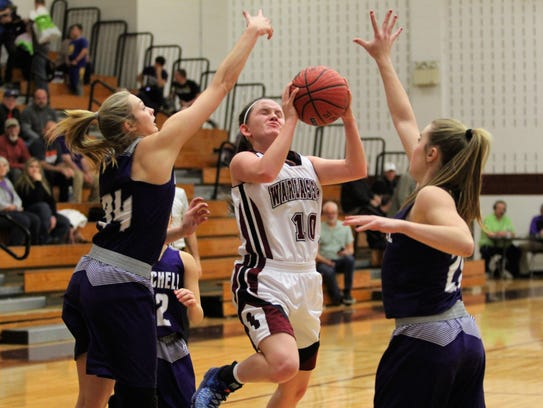 Kendal Marlowe drives to the basket against a pair of Mitchell defenders during her final regular season home game as a member of the Warlassies. The Owen senior will play basketball for Montreat College after graduation.