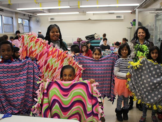 From left: Participants display the blankets they made.