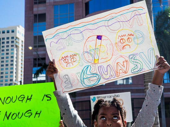 Andrea Shawfiele, 10, looks up at her handmade sign