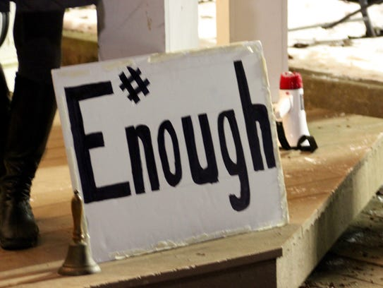 """A bronze bell sits next to a sign reading """"#Enough"""""""