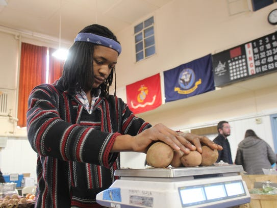 Amarree Wade, of Fishkill Farms, weighs out some produce