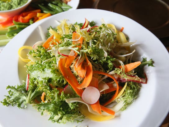 Fresh spring greens, carrot curls and sliced radishes