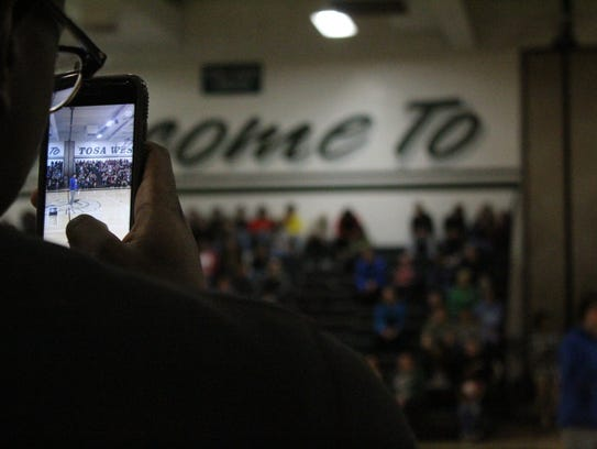 A unidentified student takes video of Wauwatosa West High School walkout on March 14. Over 400 students filed into the gym at 10 a.m