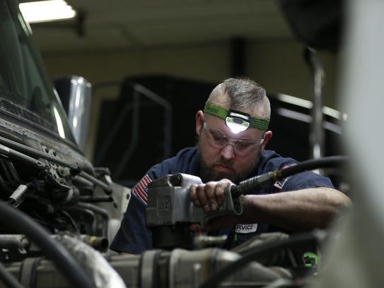 Diesel mechanic Jim Howe, 34, of Wausau, works on a