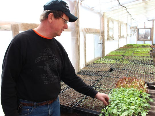 Bruce Clinger points out some of the produce growing