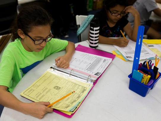 Sydney Flores, 9,  works on school work during the