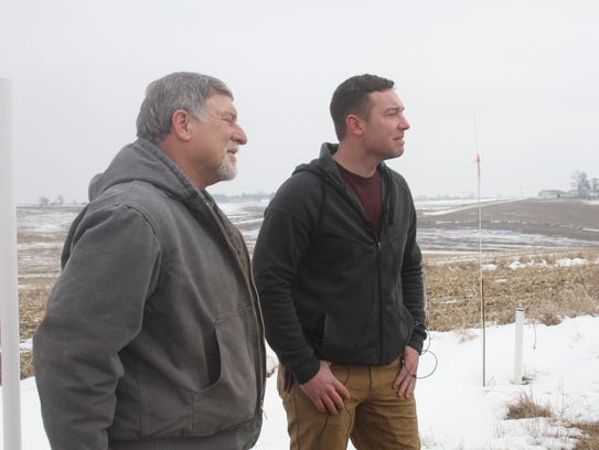 Stewart (left) and Jared Maas explain the new weather station at the family farm near South Amana.