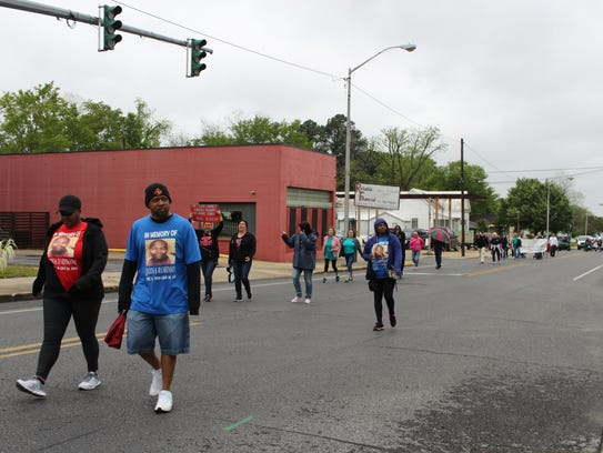 Family and friends of Chiquina Robinson walk down Main