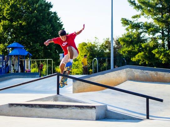 A skateboarder grinds on a rail at the skate park in